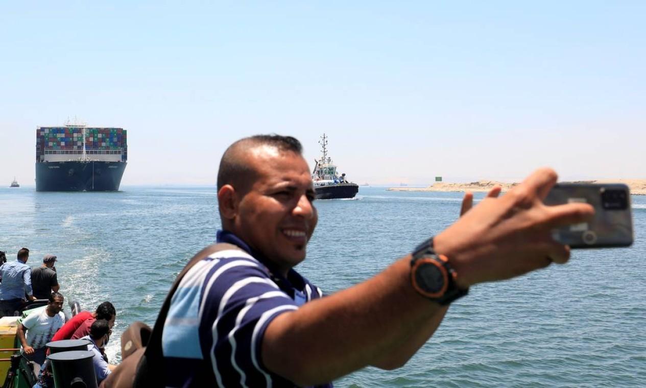 Um homem tira uma selfie tendo ao fundo o Ever Given que começou a zarpar para partir depois de quase quatro meses estacionado no Canal de Suezque, a rota marítima mais curta entre a Europa e a Ásia. Foto: AMR ABDALLAH DALSH / REUTERS