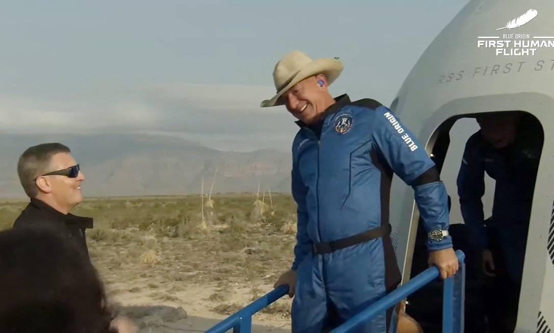 Imagem obtida do vídeo da Blue Origin mostra Jeff Bezos (à direita, usando um chapéu de caubói) deixando a cápsula da nave New Shepard,da Blue Origin, após retornar do espaço e pousar em segurança, em Van Horn, Texas. Foto: HANDOUT / AFP