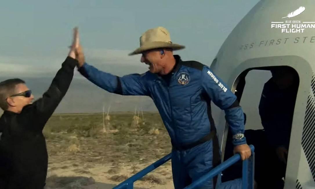 De chapéu de caubói, Jeff Bezos sai da cápsula e comemora o sucesso do voo de sua empresa Blue Origin ao espaço Foto: HANDOUT / AFP