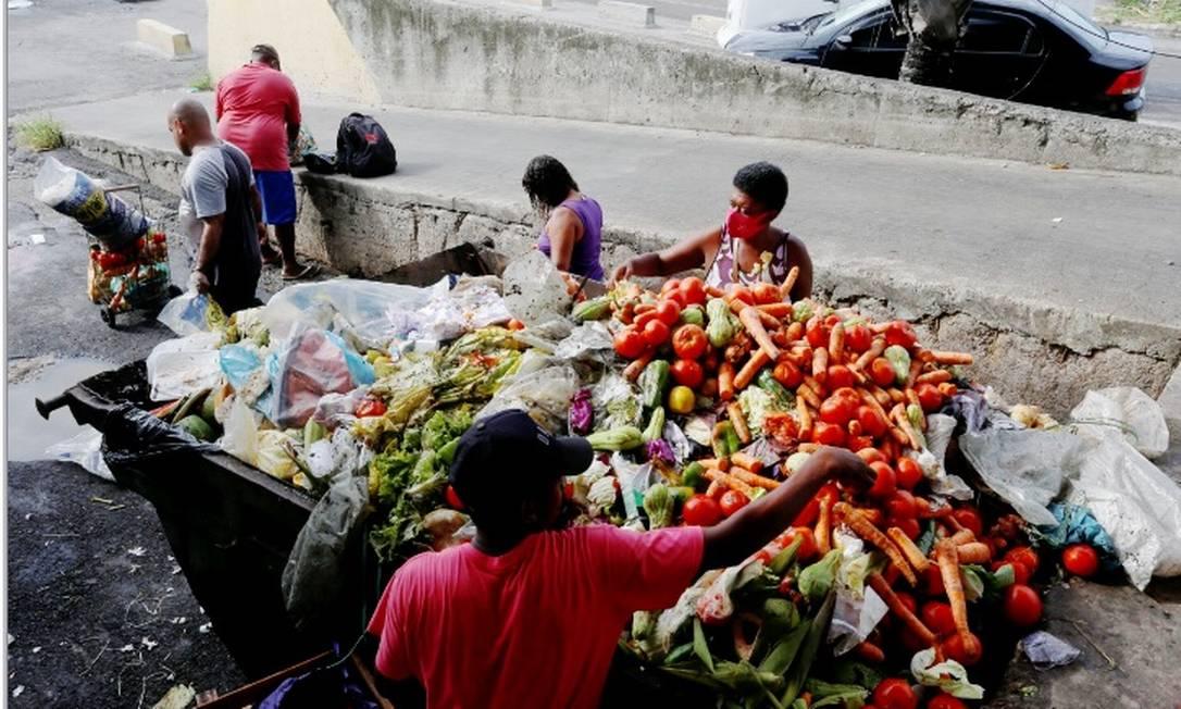 Pessoas buscam alimentos nas caçambas de lixo na Ceasa/RJ: novo programa vai elevar valor da linha da pobreza Foto: Fabiano Rocha/Agência O Globo