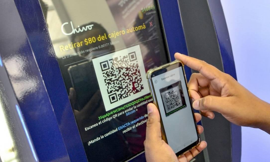 Salvadorenho faz operação com bitcoin em caixa eletrônico Foto: Bloomberg