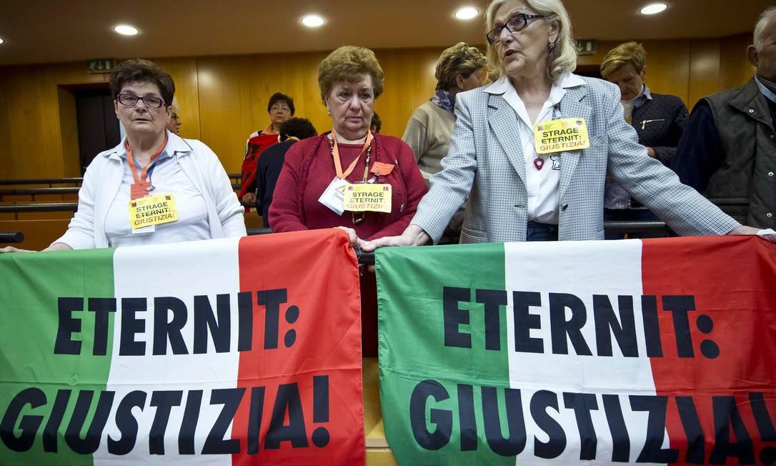 """Parentes e vítimas de vítimas mostram bandeiras em que se lê: """"Eternit: Justiça"""", na corte de Turim Foto: Marco Alpozzi / AP"""