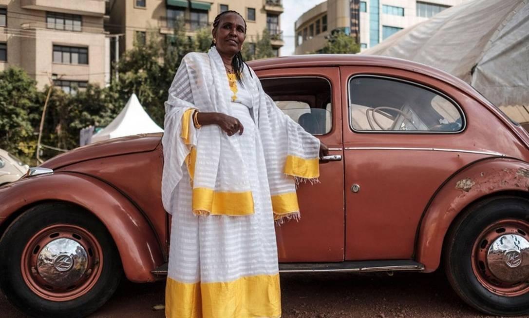 Fidelidade. Senhora com roupas típicas etíopes posa com seu Fusca alemão Foto: Eduardo Soteras/AFP