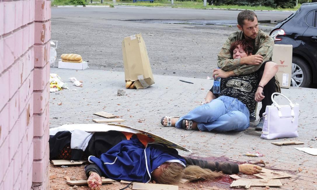 Na Ucrânia, em 2014, uma mulher tenta socorrer parente ferido após ataque Foto: Jonathan Alpeyrie