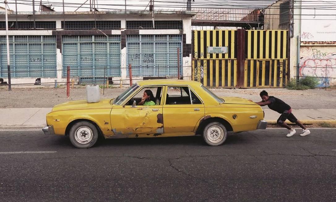 Um jovem empurra um carro até um posto de gasolina em Maracaibo, cidade venezuelana que também sofre com a falta de luz e de água potável. Foto: Edilzon Gamez / Getty Images