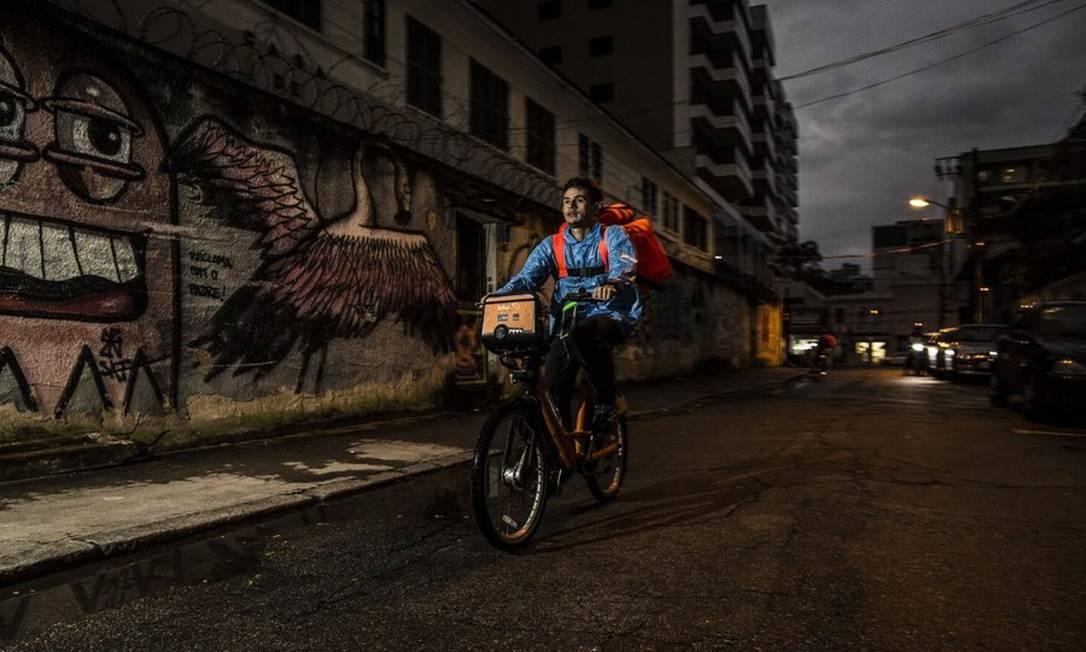 O venezuelano Daniel Rabón, que vende passeios no calçadão de Copacabana, no Rio de Janeiro, durante a manhã e roda a cidade como entregador de aplicativo à tarde e à noite. Foto: Guito Moreto / Agência O Globo