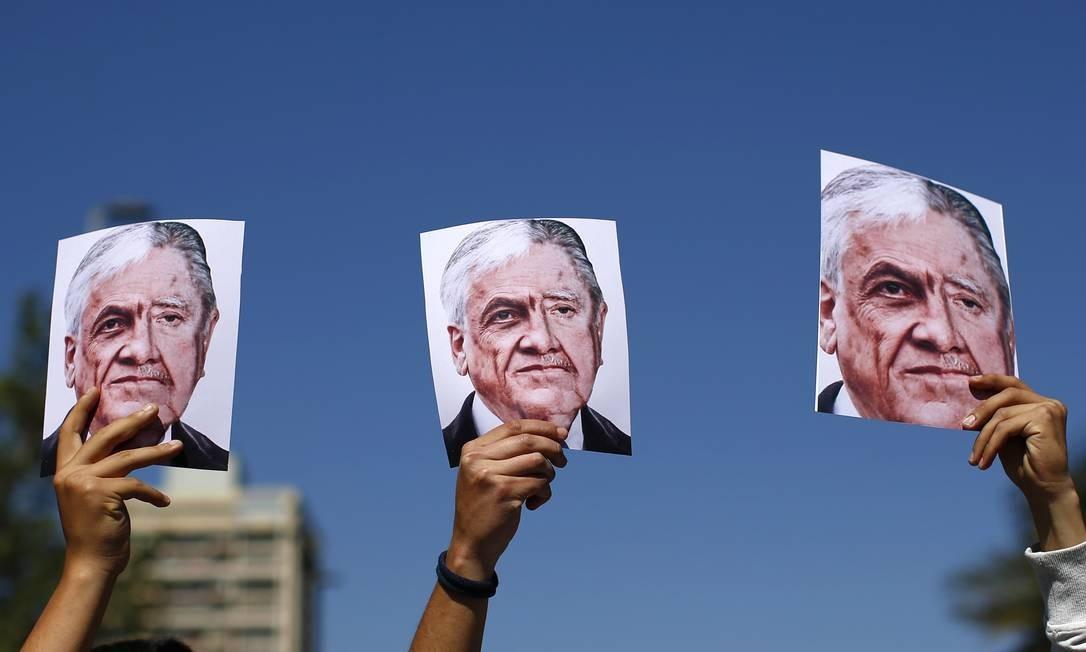 Manifestantes erguem montagens que mesclam fotos do presidente chileno, Sebastián Piñera, e do ditador Augusto Pinochet, durante um dos dias de protesto nas ruas de Santiago. Foto: Pablo Vera / AFP