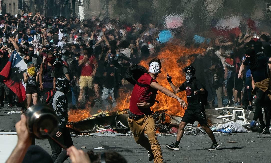 Cenas de violência e confronto foram recorrentes nas manifestações que eclodiram no Chile Foto: Pedro Ugarte / AFP