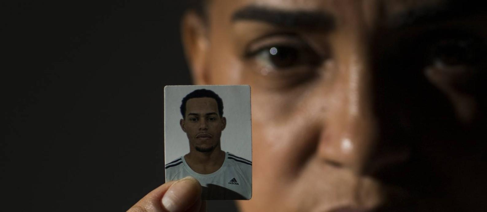 Ana Cláudia Rangel, com a foto do filho Daniel Souza, frentista que se preparava para entrar na faculdade, mas foi morto pela polícia e apresentado como criminoso. Foto: Guito Moreto / Agência O Globo