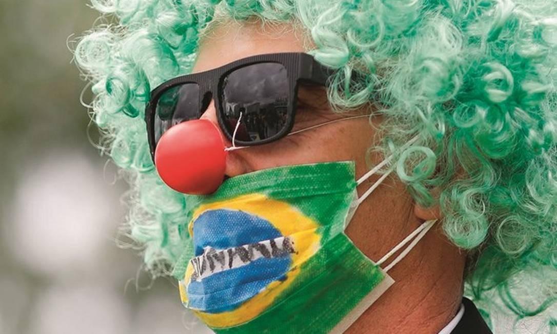 Um apoiador de Jair Bolsonaro se veste de palhaço e usa máscara em protesto em Brasília, no dia 15. O presidente esteve presente. Foto: Sergio Lima / AFP