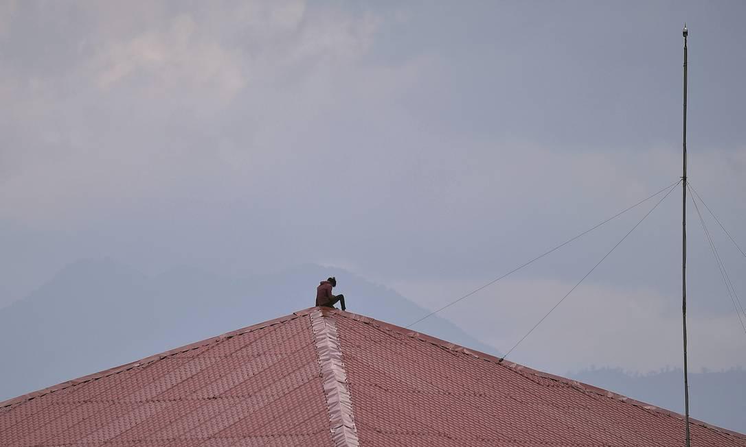 Uma funcionária de uma empresa no Nepal aproveita o momento de folga no trabalho, em uma construção, para olhar seu celular. Foto: NurPhoto / Getty Images