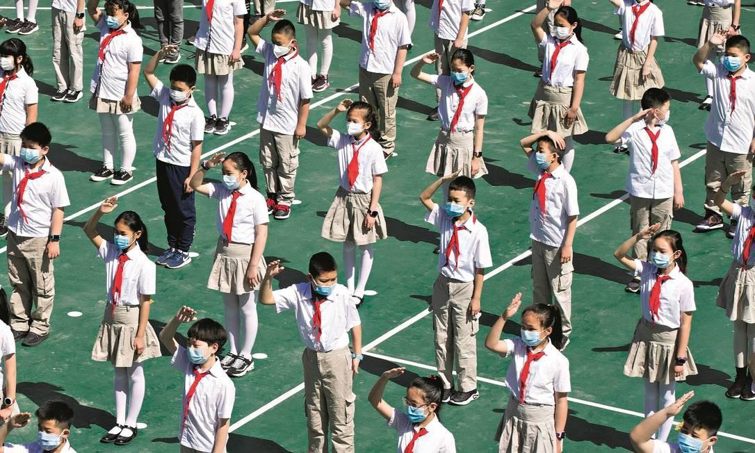 Estudantes fazem distanciamento social ao hastearem a bandeira chinesa na escola, em Taiyuan. A retomada das aulas presenciais no país começou em abril. Foto: China News Service via Getty Images