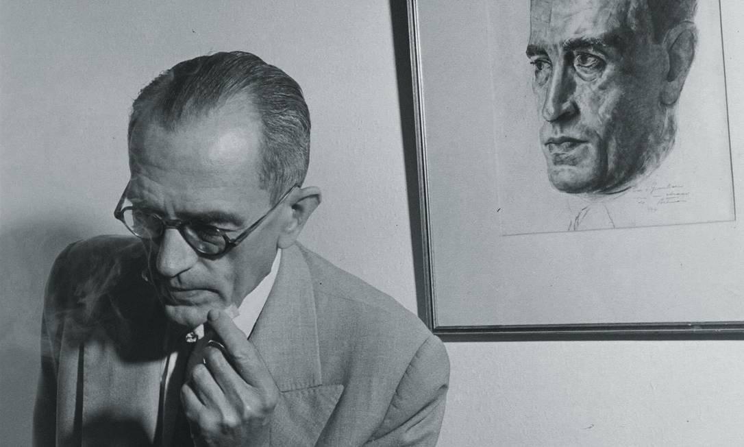 Graciliano Ramos em sua casa, em 1952, em frente ao retrato feito pelo amigo Candido Portinari. Foto: Kurt Klagsbrunn