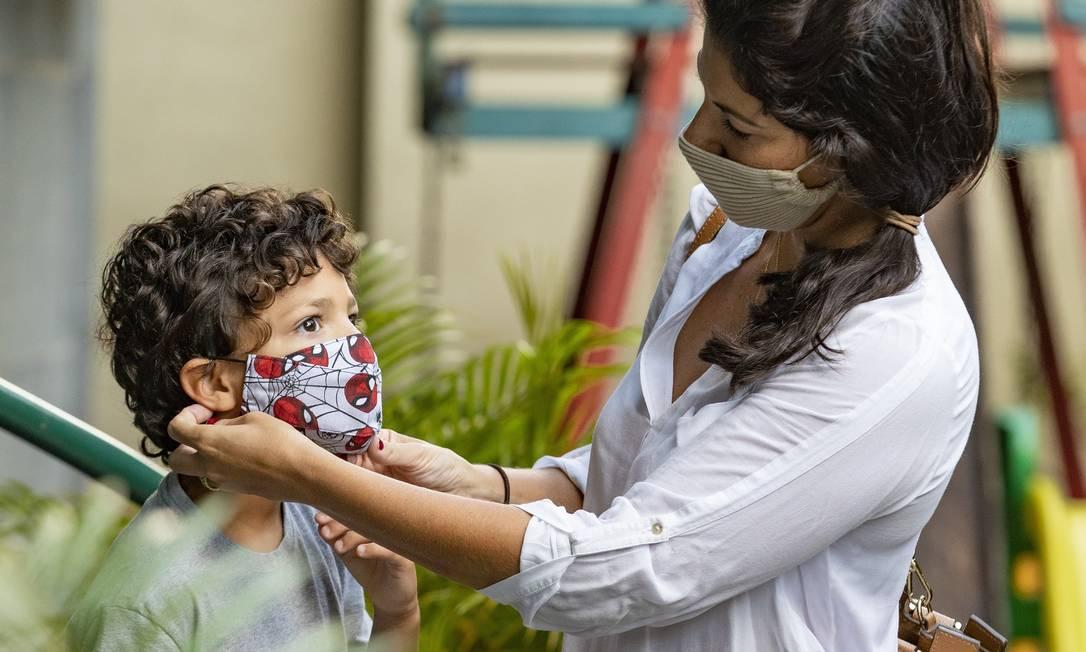 Vanessa Borges ajuda o filho, Gabriel, a colocar a máscara. Ele teve Covid-19 e passou a pedir para usar o EPI sempre que sai de casa. Foto: Ana Branco / Agência O Globo