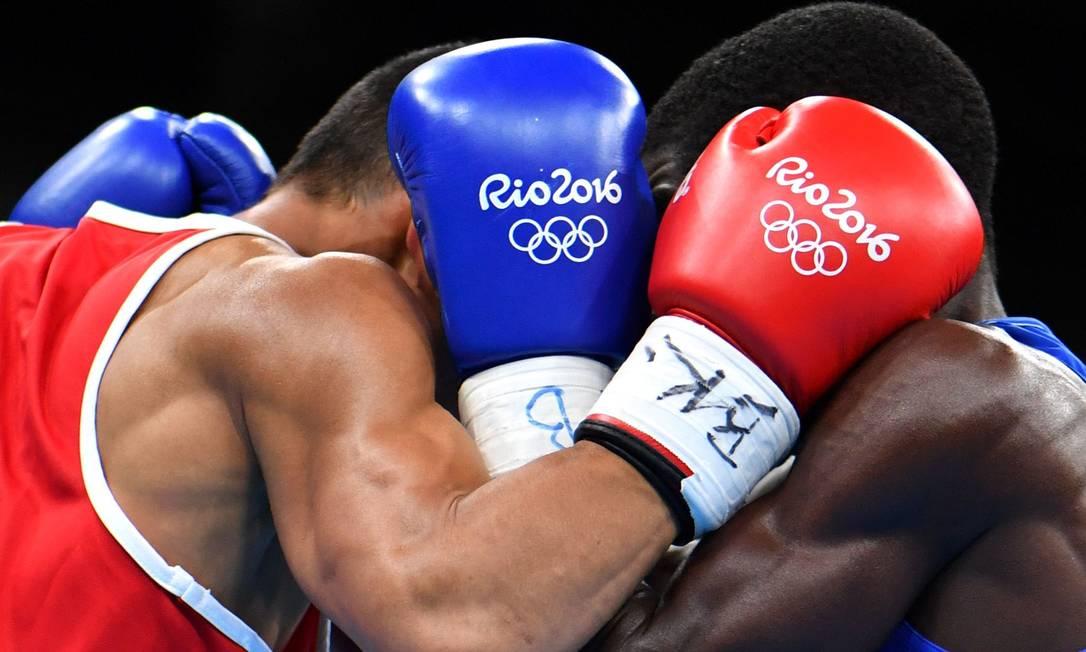 O filipino Rogen Ladon (à direita) durante luta contra o colombiano Yurberjen Herney Martinez na categoria (46-49kg) YURI CORTEZ / AFP