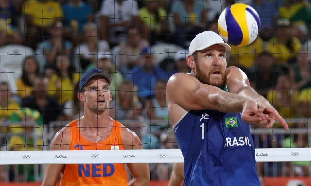 Alison, observado pelo jogador holandês, lança a bola para a quadra adversária Marcelo Carnaval / Agência O Globo