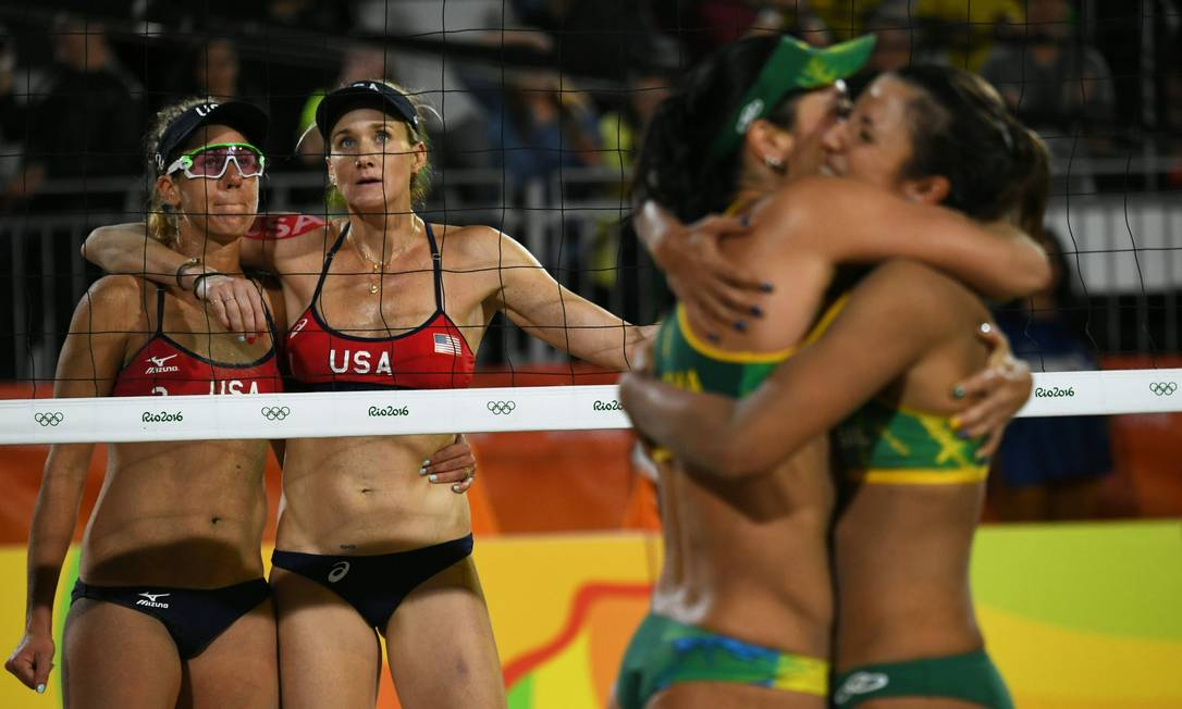 Kerri Walsh e April Ross observam Larissa e Talita, que se abraçam depois de vencerem o primeiro set YASUYOSHI CHIBA / AFP