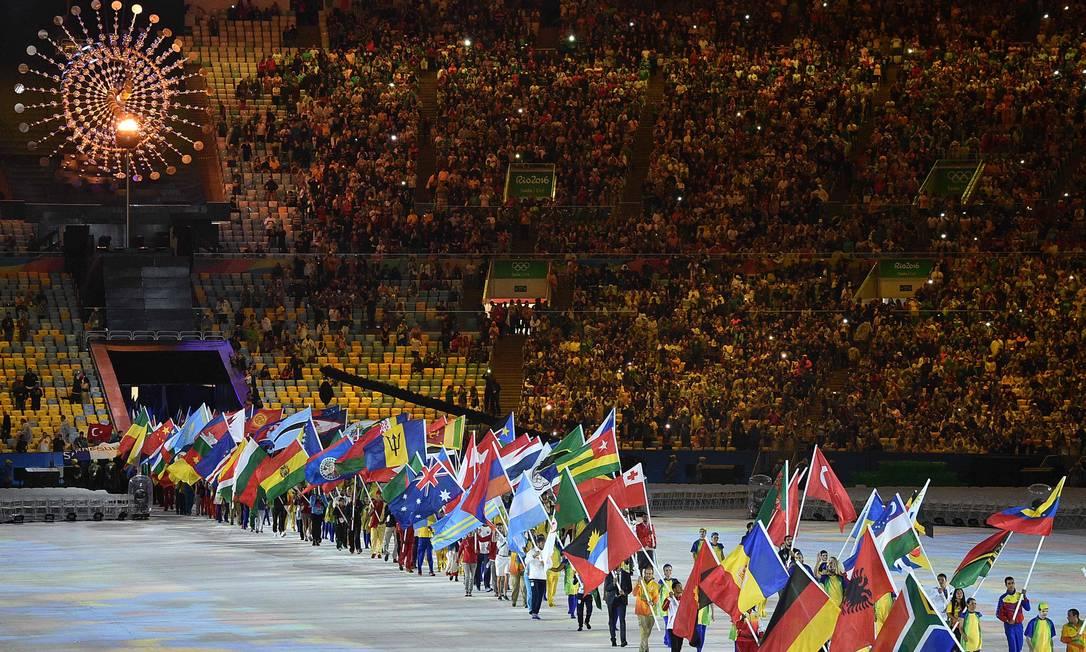 Atletas desfilam com as bandeiras de seus países na cerimônia de encerramento da Olimpíada LUIS ACOSTA / AFP