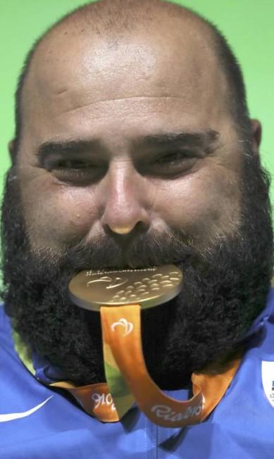O grego Pavlos Mamalos, do levantamento de peso, posa com a medalha de ouro UESLEI MARCELINO / REUTERS