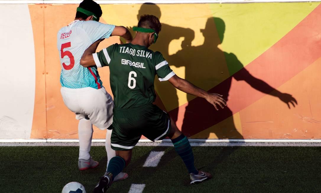 O brasileiro Thiago Silvia disputa a bola com Recep Aydeniz, da Turquia, durante partida do futebol de 5 CHRISTOPHE SIMON / AFP