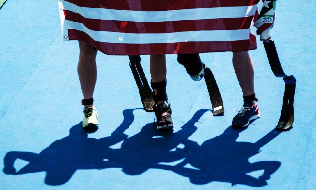 As americanas Allysa Seely, Hailey Danisewicz e Melissa Stockwell posam com a bandeira de seu país durante o triatlo YASUYOSHI CHIBA / AFP