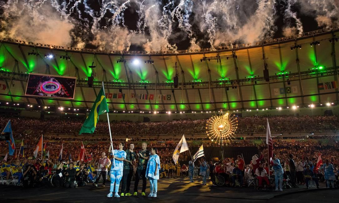 Ricardinho, do futebol de 5, carrega a bandeira do Brasil; ao fundo, a pira paralímpica Thomas Lovelock for OIS/IOC / Agência O Globo