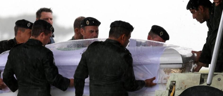 Caixões são retirados das aeronaves Foto: PAULO WHITAKER / REUTERS