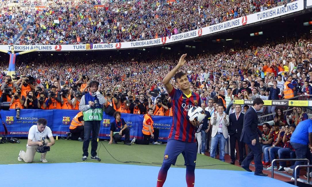 No Camp Nou lotado com mais de 45 mil pessoas, Neymar chega ao Barcelona em 3 de junho de 2013. A transferência custou € 57 milhões. A venda causou confusão porque o clube catalão revelou, em sua página na web, que pagara €10 milhões antecipadamente ao atacante brasileiro, em novembro de 2011. Santos e o grupo de investimentos DIS brigaram na Justiça pelas comissões sobre a venda e ambos acionaram a Fifa contra o Barcelona. Foto: GUSTAU NACARINO / Reuters