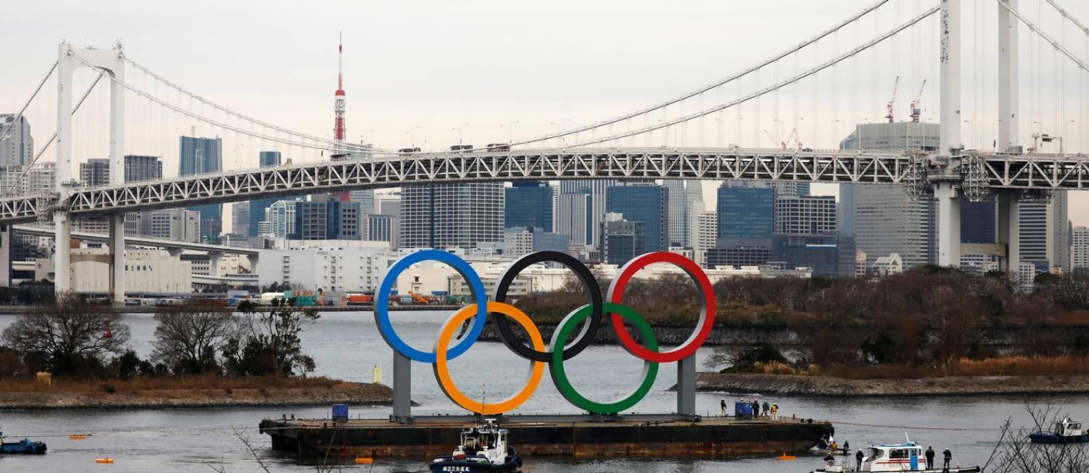Estrutura com os Anéis Olímpicos, com 15,3 metros de altura e 32,6 metros de comprimento, no Parque Marinho de Odaiba, com vista para os arranha-céus da capital japonesa e da Rainbow Bridge (Ponte de Arco-Íris), será inaugurada nesta sexta-feira, para marcar os seis meses dos Jogos Foto: ISSEI KATO / REUTERS