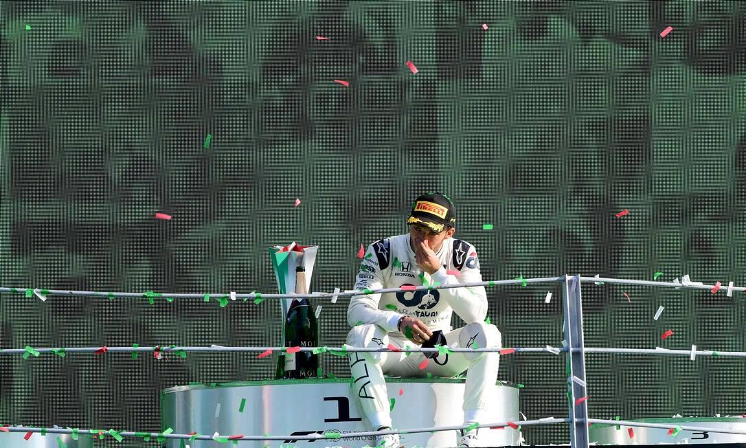 Pierre Gasly parece não acreditar na vitória conquistada em Monza, na Itália: ele senta no pódio após estourar a champanhe Foto: JENNIFER LORENZINI / AFP