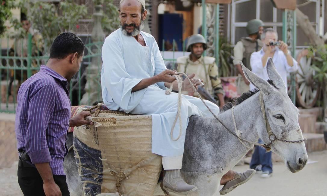 Policial revista dono de burro em subúrbio do Cairo. No sábado, um fazendeiro foi preso por dar nome de general a seu animal Foto: MOHAMED ABD EL GHANY / REUTERS