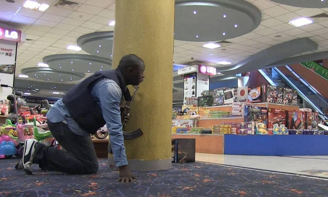 Policial queniano se esconde atrás de pilastra em confronto com radicais dentro do shopping Westgate Foto: Nichole Sobecki / AFP