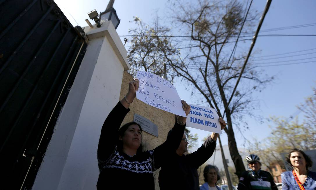 Manifestantes protestam contra um churrasco na prisão organizado por Miguel Krassnoff, um ex-agente do serviço de inteligência da ditadura de Pinochet, em frente à prisão Cordillera em Santiago Foto: IVAN ALVARADO / REUTERS