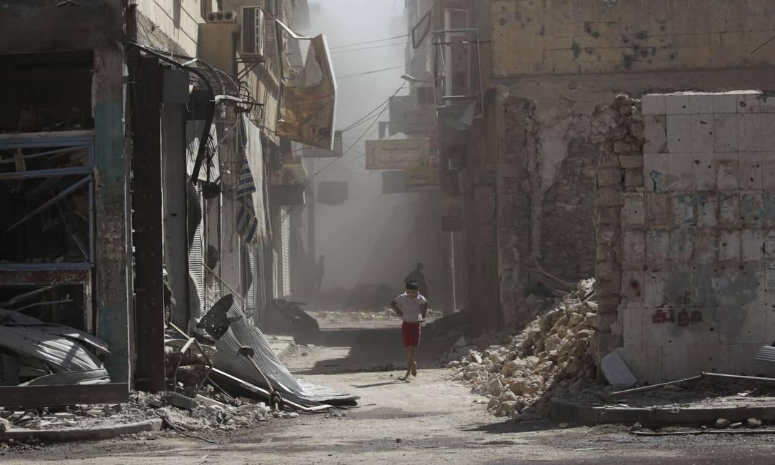 Menino anda por ruas destruídas por bombardeios em Deir al-Zor Foto: STRINGER / REUTERS