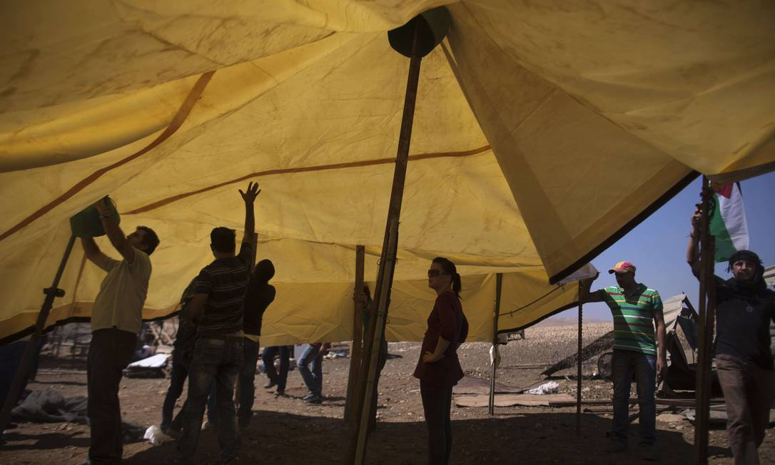 Ativistas palestinos e israelenses erguem novas barracas em acampamento demolido pelo Exército de Israel Foto: MENAHEM KAHANA / AFP