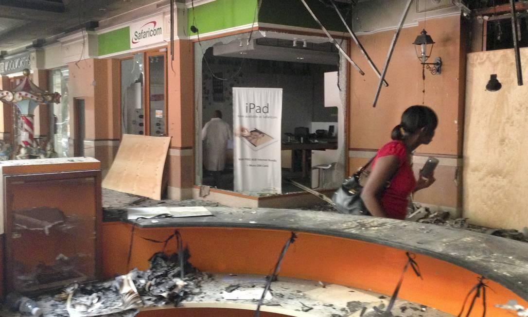Uma mulher passa diante de uma loja de celulares destruída Foto: Jason Straziuso / AP