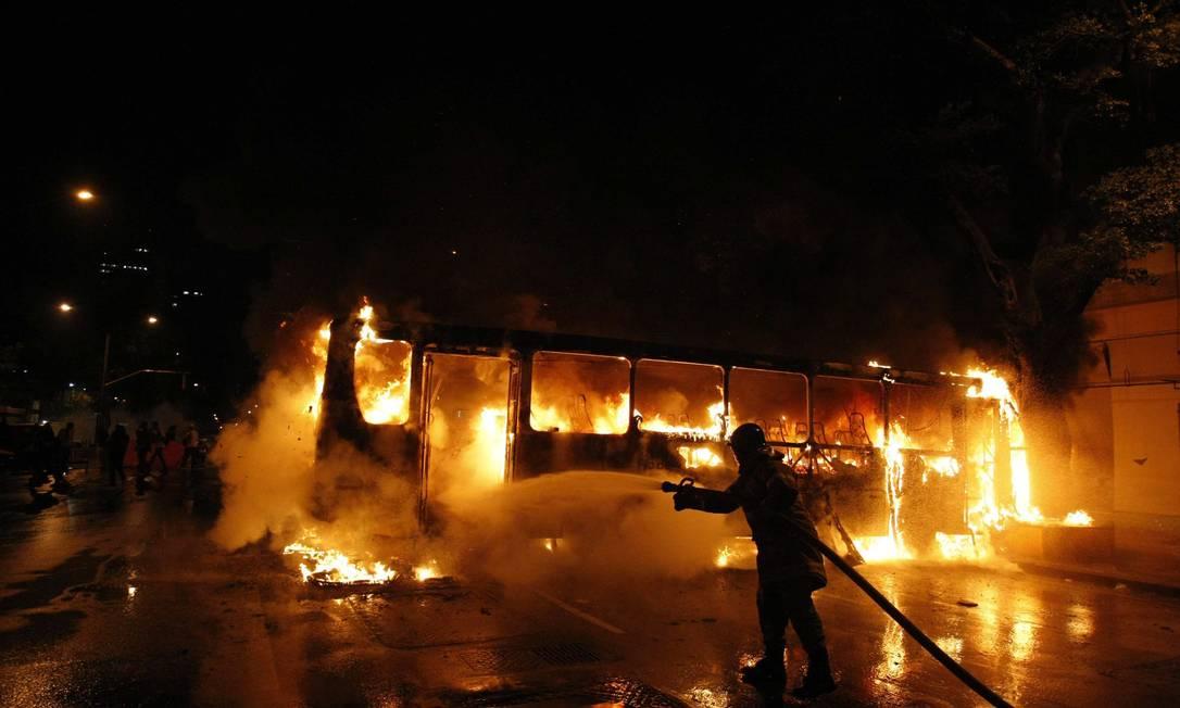 Bombeiro apaga as chamas de ônibus incendiado por vândalos Foto: Pablo Jacob / Agência O Globo