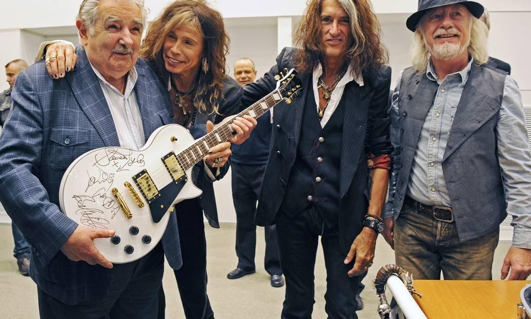 O presidente uruguaio recebe uma guitarra e abraços dos integrantes da banda americana Foto: HANDOUT / Reuters