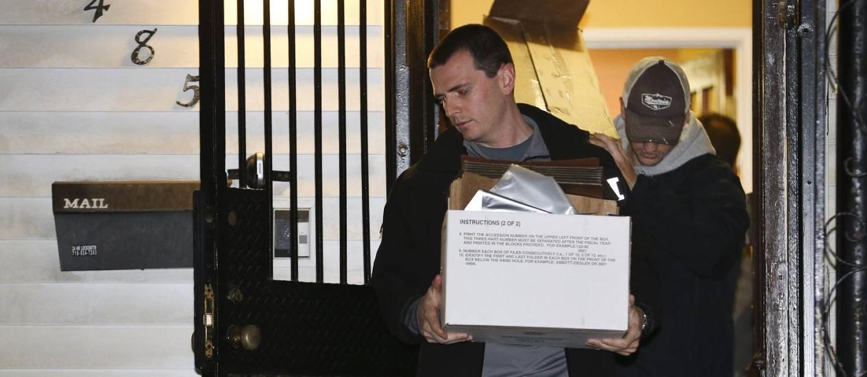 Agentes do FBI retiram provas da casa do rabino Mendel Epstein, na noite de terça-feira Foto: John Minchillo / AP