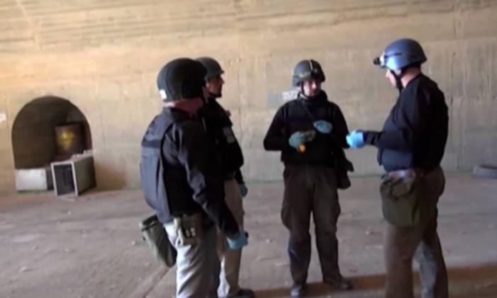 Imagem da TV síria mostra inspetores da Opac trabalhando em um local secreto no país árabe em 10 de outubro Foto: - / AFP
