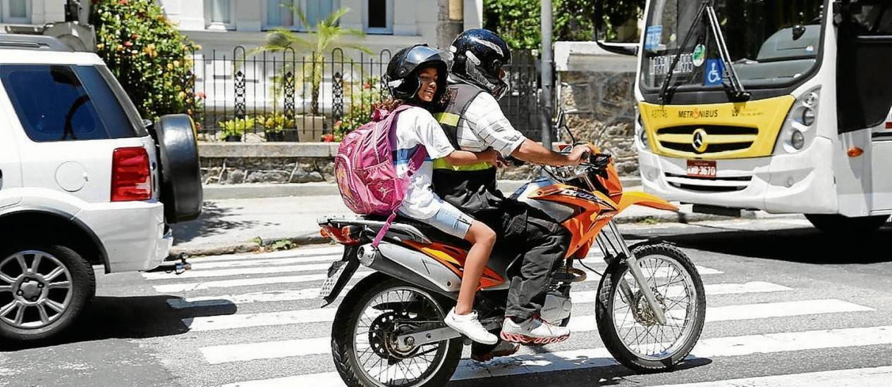 Criança viaja em garupa de moto em Laranjeiras: vaivém é grande na porta de escolas Foto: Alexandre Cassiano / Agência O Globo