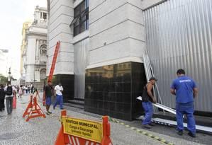 Segurança reforçada. Funcionários instalam chapa de aço na fachada do Edifício Municipal, no Centro do Rio Foto: Pedro Kirilos / O Globo