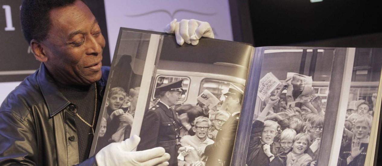 Pelé com o livro que terá 500 imagens e 1.283 textos sobre o Rei do Futebol Foto: Eliaria Andrade / O Globo