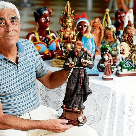 Manoel Esteves Machado, o Tito, com a imagem de São Francisco: todas as esculturas são de gesso e feitas a mão Foto: Agência O Globo / Daniela Dacorso