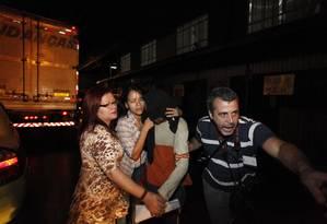 Familiares escondem rostos de presos, libertados do Complexo de Gericinó na noite de sexta-feira Foto: Pablo Jacob / Agência O Globo