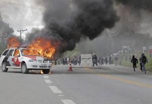 Pelo menos dois carros da imprensa e um da polícia foram incendiados por um grupo de mascarados Foto: Eliaria Andrade/ O Globo