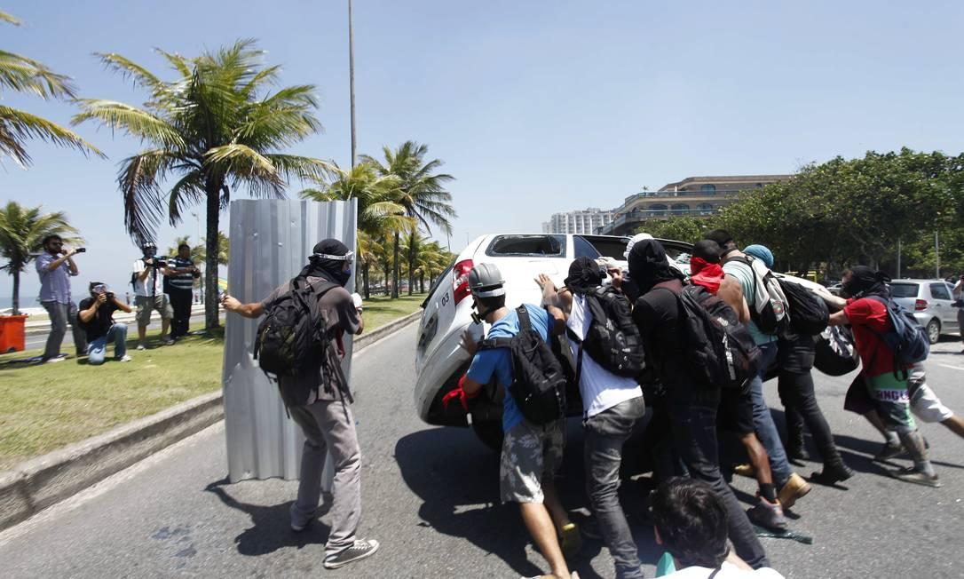 Manifestantes viram um carro durante confronto com a polícia Pablo Jacob / Agência O Globo