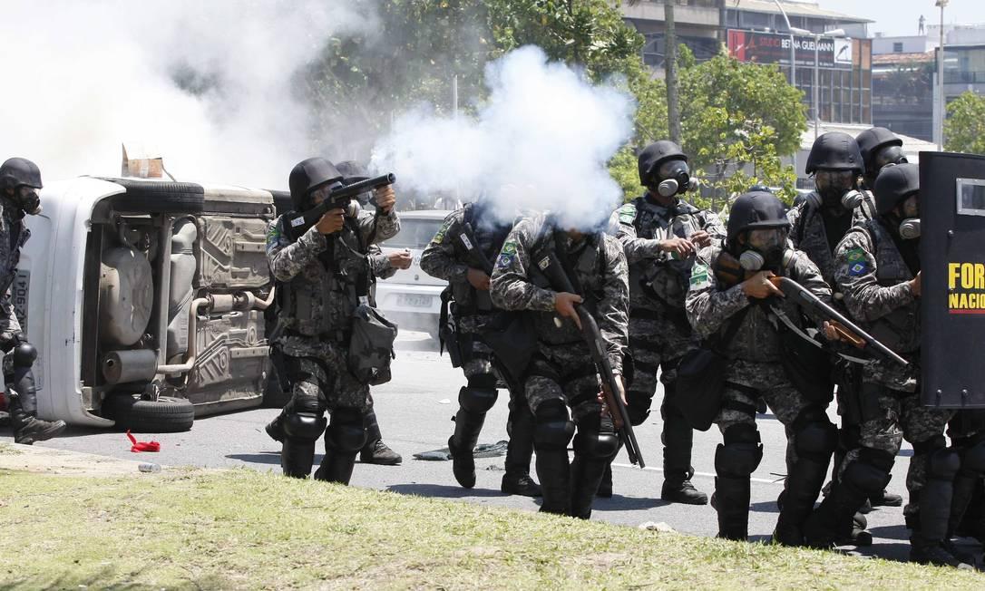 Policiais enfrentam manifestantes durante protesto contra o leilão do poço de Libra, na Barra da Tijuca Pablo Jacob / Agência O Globo