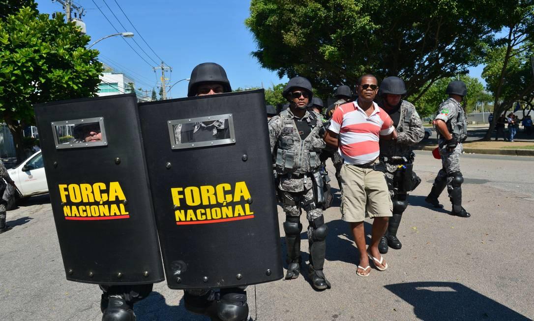 Um homem é detido por soldados da Força Nacional durante protesto contra o leilão de Libra CHRISTOPHE SIMON / AFP