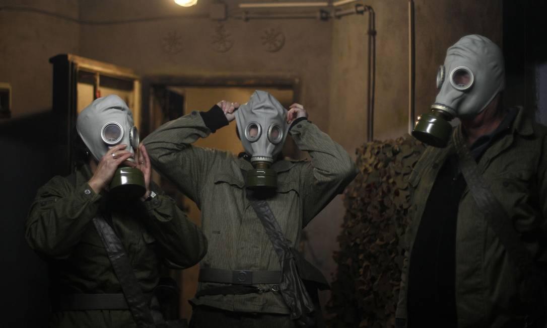 Membros da família Hoppmann usam máscaras de gás durante o tour pelo bunker Foto: Ina Fassbender / Reuters